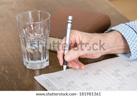 Close up of senior man's hand in pajamas, solving crosswords - stock photo