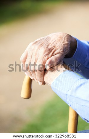 Close Up Of Senior Man's Hands Resting On Walking Stick - stock photo