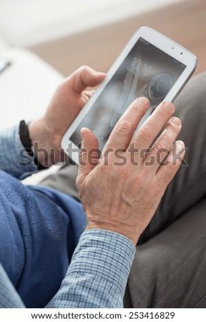 Close-up of senior man using his tablet - stock photo