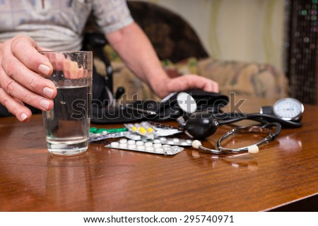 Close Up of Senior Man with Heart and Blood Pressure Medications and Medical Supplies Scattered on Table - stock photo