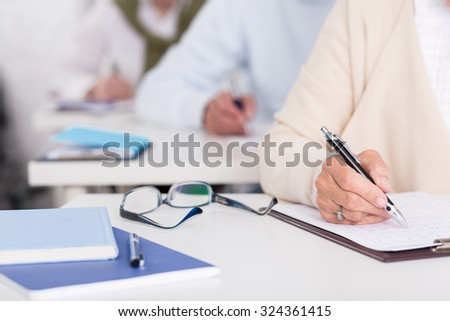 Close up of senior students during written exam - stock photo
