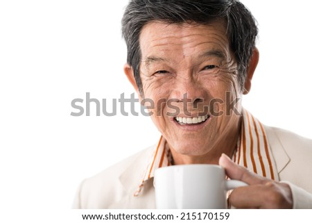 Close-up of senior Vietnamese man drinking tea - stock photo