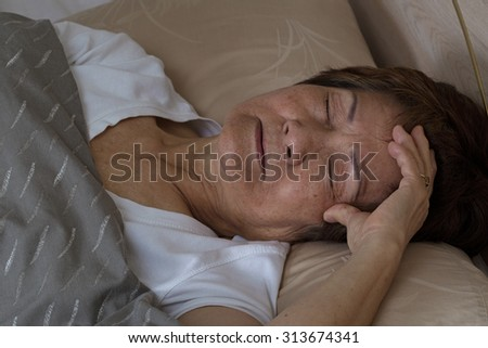 Close up of senior woman, eyes close, trying to fall asleep. Insomnia concept.  - stock photo