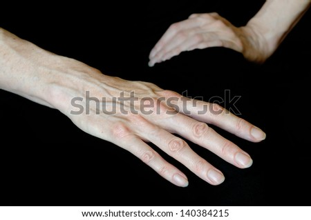 Close up of senior woman's hands in different positions on black background. Here one open hand shows long fingers