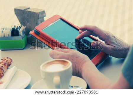close up of senior woman's hands with tablet - stock photo