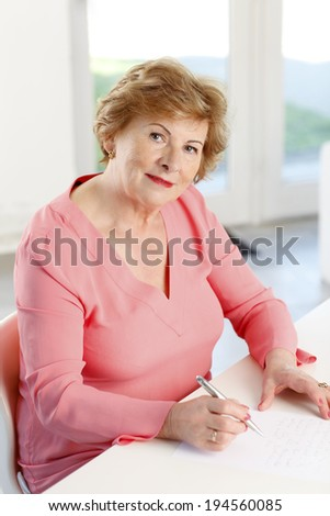 Close-up of senior woman sitting at desk and making the list.  - stock photo