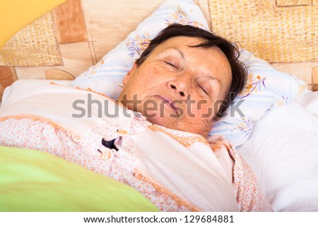 Close up of senior woman sleeping in bed. - stock photo