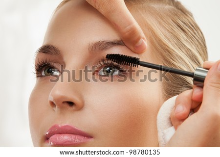 Close-up of separating and curling lashes process with mascara brush - stock photo