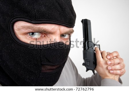 Close-up of serious armed criminal with gun - stock photo