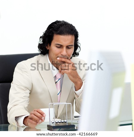 Close-up of serious businessman playing with kinetic balls in the office - stock photo