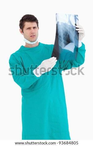 Close up of serious looking doctor with x-ray against a white background