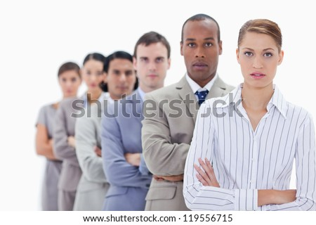 Close-up of serious people dressed in suits crossing their arms in a single line with focus on the first woman - stock photo