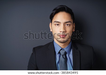 Close up of serious single young bearded male manager in blue jacket, shirt and necktie with copy space in dark background - stock photo
