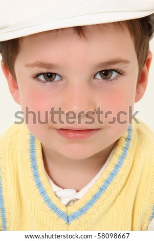 Close up of serious three year old boy wearing white kangol and yellow sweater vest. - stock photo