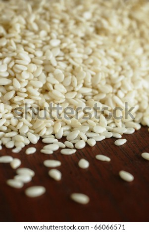 Close up of sesame seeds on a wood table - stock photo