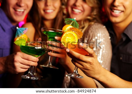 Close-up of several cocktails in young people hands - stock photo