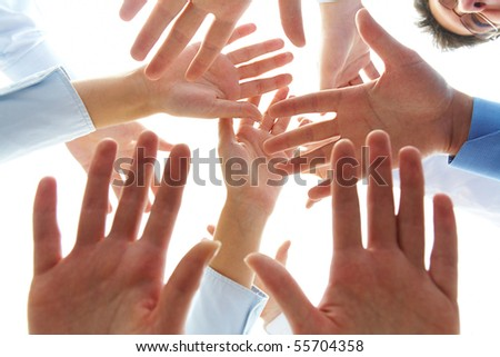 Close-up of several human palms over camera - stock photo
