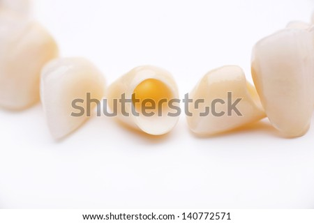 Close-up of several prosthetic teeth isolated on white background - stock photo