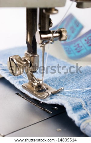 Close-up of sewing machine with blue cotton - stock photo