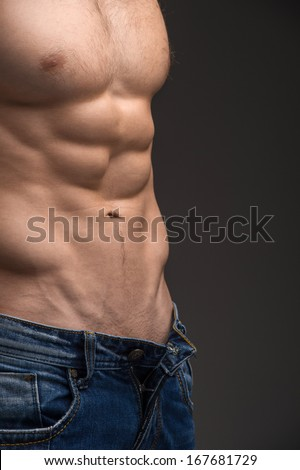 Close up of Sexy muscular nude male torso. Wearing unbutton jeans and posing isolated over dark background