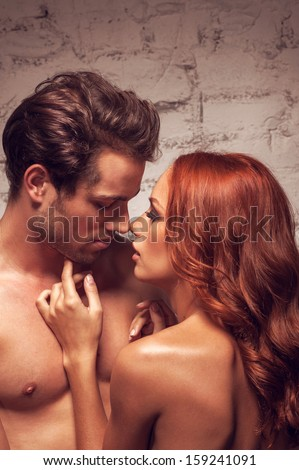 Close up of sexy nude couple going to kiss. Beautiful girl touching man face  - stock photo