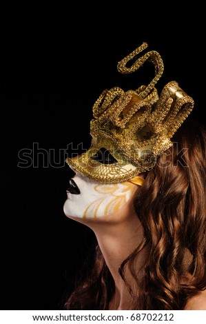 close up of sexy woman in golden party mask isolated on black