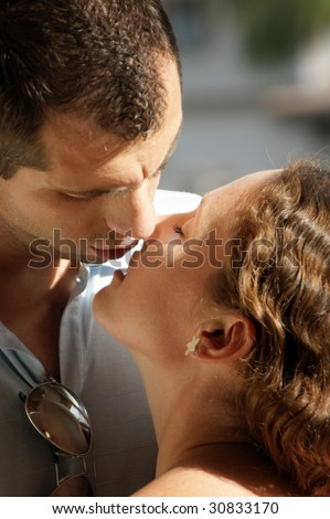 close up of sexy young couple about to kiss in the hot afternoon sunshine with their lips parted ready to meet - stock photo