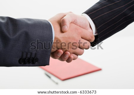 Close-up of shaking hands making an agreement on the background of folder and pen