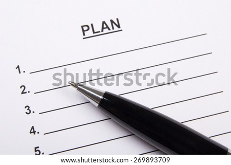 close up of sheet of paper with plan and metal pen - stock photo
