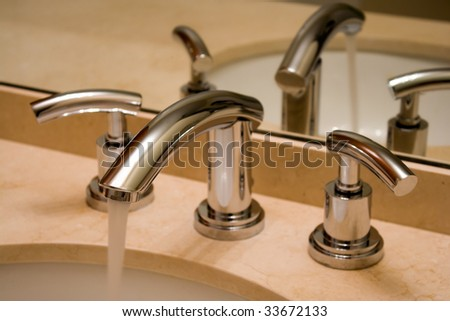 Close up of shiny chrome faucet in modern luxury bathroom. - stock photo