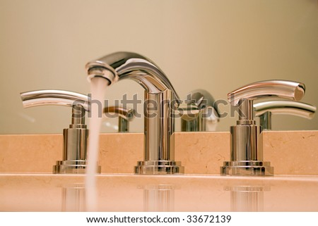 Close up of shiny chrome faucet in modern luxury bathroom.