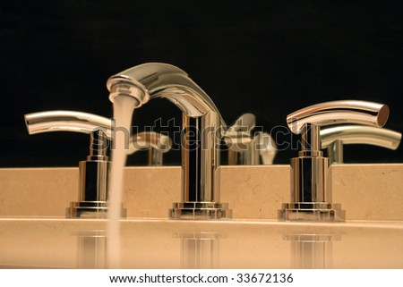 Close up of shiny chrome faucet on black background in modern luxury bathroom. - stock photo