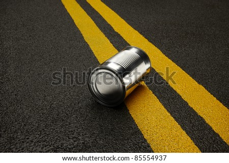 Close up of shiny metal can sitting on an black asphalt road with yellow stripes - stock photo