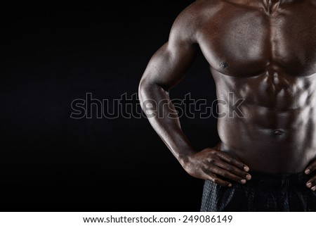 Close-up of shirtless african man with hands on hip while standing against black background. Cropped image of torso of a muscular man with copyspace. - stock photo