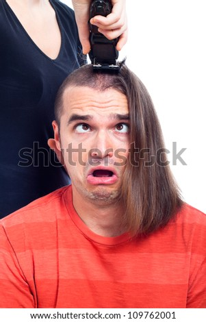 Close up of shocked long haired man being shaved with hair trimmer, isolated on white background.