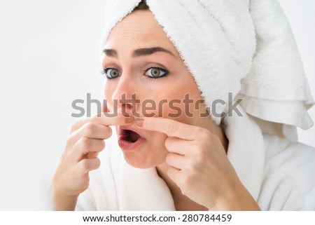 Close-up Of Shocked Woman Looking At Pimple On Face - stock photo