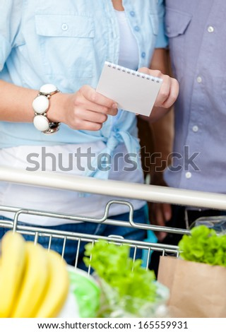 Close up of shopping list in hands of couple standing near the cart full of food - stock photo