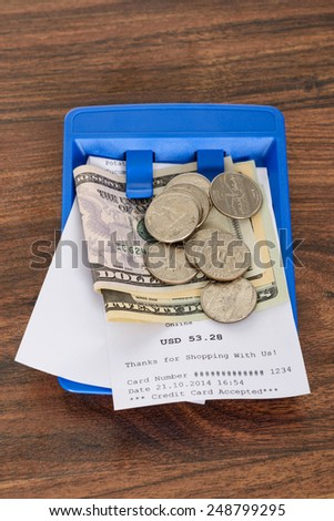 Close-up Of Shopping Receipt With American Dollars On Blue Tray - stock photo