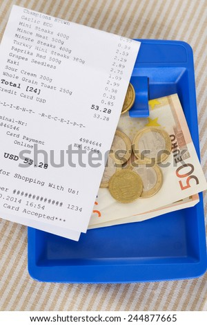 Close-up Of Shopping Receipt With Euro Notes On Wooden Table - stock photo