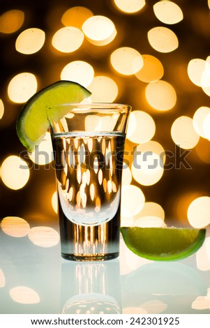 Close up of shots glass and limes with bokeh background - stock photo