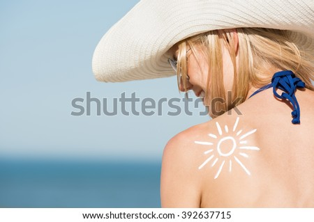 Close up of shoulder of beautiful woman with a sun drawn with the suntan lotion. Back pose of girl wearing hat and sunglasses at beach. Beautiful woman sunbathing with a sunscreen lotion on shoulder. - stock photo
