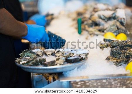 close-up of shucking fresh oysters and arranging them on the plate in restaurant - stock photo