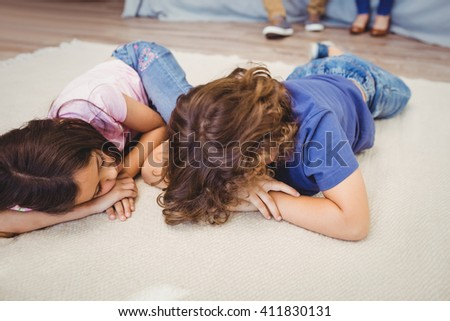 Close-up of siblings relaxing on carpet at home - stock photo