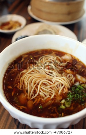 Close up of Sichuan Ramen with other dishes on table. - stock photo
