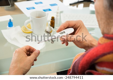Close-up Of Sick Businessman Looking At Temperature In Thermometer - stock photo