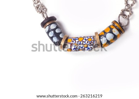 Close up of silver and painted stone necklace isolated on white background, manufactured by Ornella Salamone - stock photo