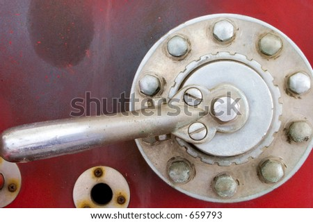 Close up of silver or steel lever against rusted, old red background suggesting leverage or handling leverage or controlling. - stock photo