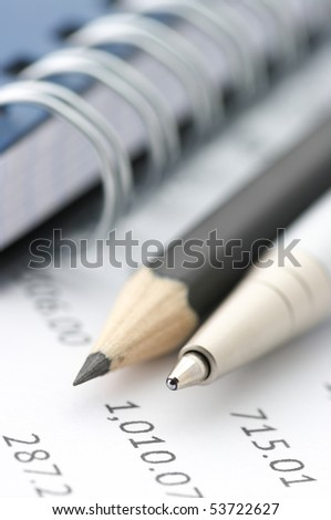 Close-up of silver pen, black pencil and notepad on paper table numbers. - stock photo