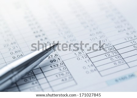 Close up of silver pen lying on the financial document with copy - stock photo