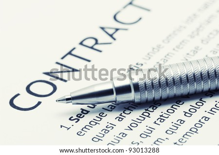 Close-up of silver pen on contract. Toned image. - stock photo